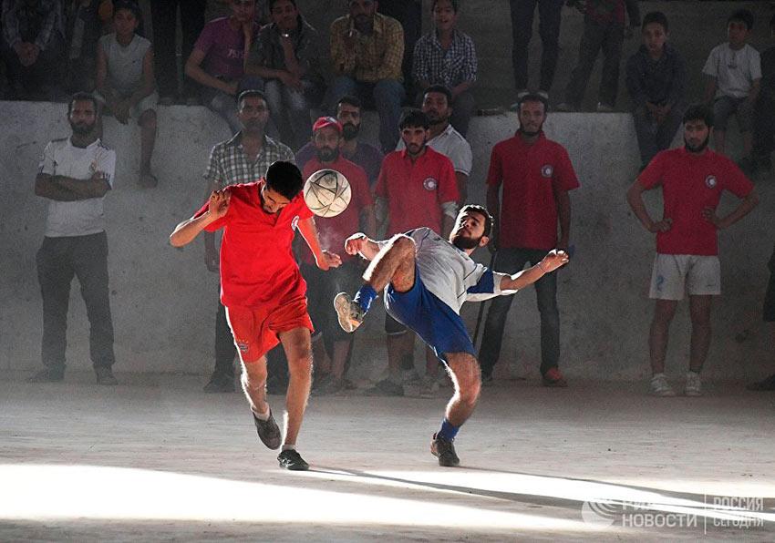 Лучшие фотографии апреля Футбольный матч между командами сотрудников общества Красного Креста и Красного Полумесяца и студентами в сирийском городе Дейр-эз-Зор