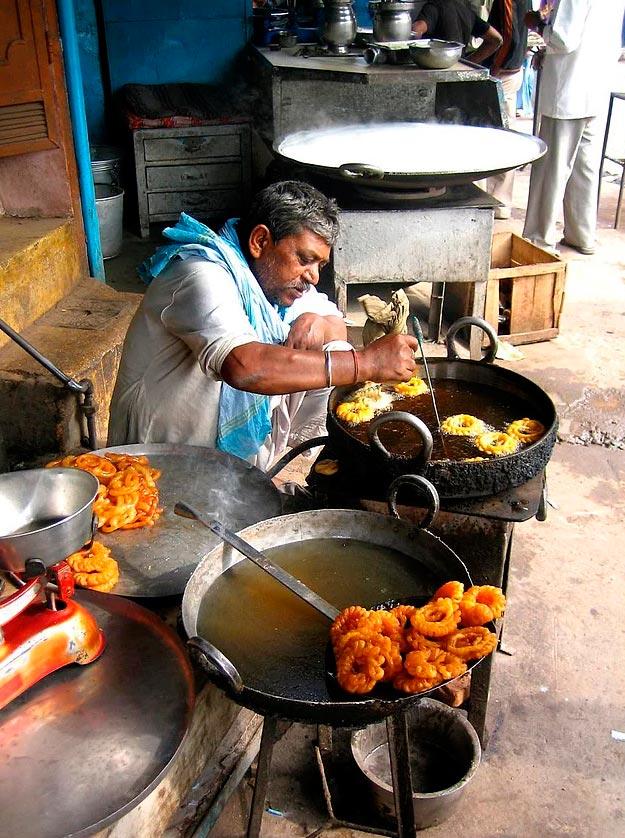 Продавцы уличной еды из разных уголков планеты продавец индийских сладостей джалеби в Дели (Индия).