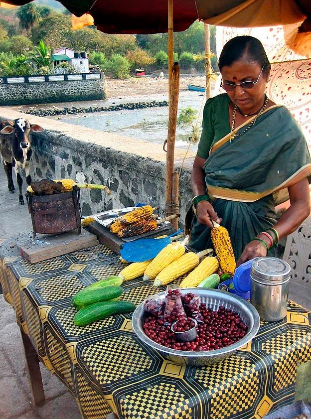 Продавцы уличной еды из разных уголков планеты торговка кукурузой на гриле в Мумбаи (Индия).