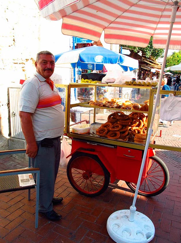 Продавцы уличной еды из разных уголков планеты продавец турецкого уличного лакомства - симитов (бублики с кунжутом).