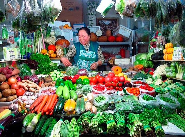 Продавцы уличной еды из разных уголков планеты продавщица овощей в Пекине (Китай).